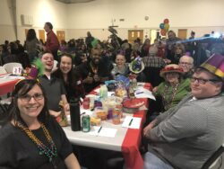 Table of 8 people dressed in Mardi Gras hats and beads